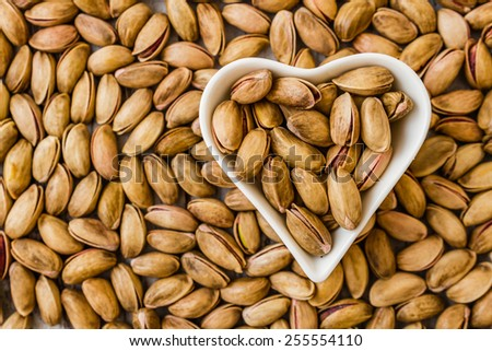 Pistachio nuts in a heart shaped white ceramic bowl - stock photo