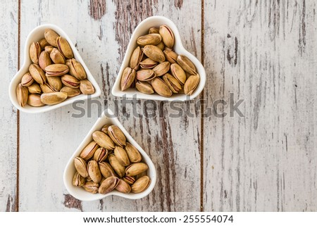 Pistachio nuts in heart shaped ceramic bowls on white wooden background - stock photo