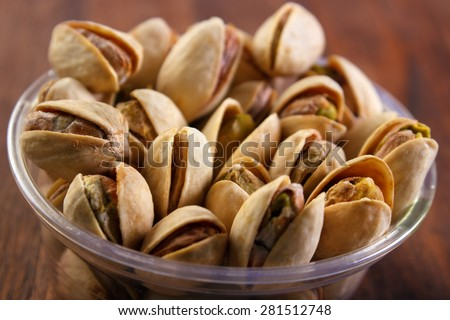 Pistachio nuts in plastic cup closeup , dark wooden background , shallow DOF - stock photo