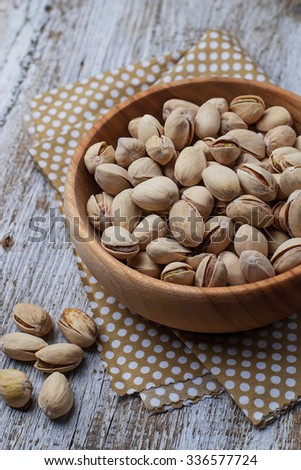 Pistachio nuts in wooden bowl. Selective focus - stock photo