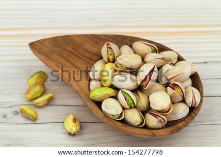 Pistachio nuts with and without shell in wooden bowl  - stock photo