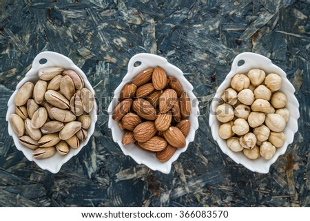 Pistachios, almonds and hazelnuts in white bowls on blue background - stock photo