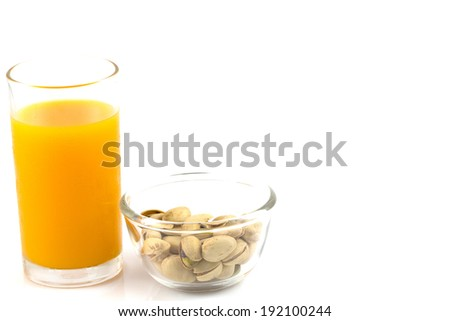 pistachios in a glass plate and glass of orange juice isolated on white - stock photo