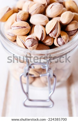 Pistachios in the glass jar,selective focus - stock photo