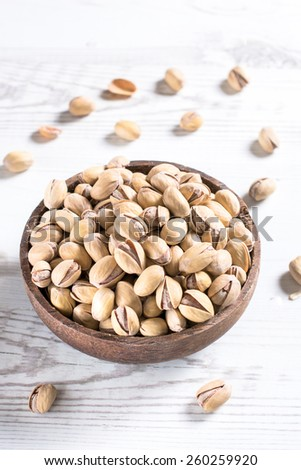 Pistachios in the wooden bowl from above,selectiv focus and blank space   - stock photo