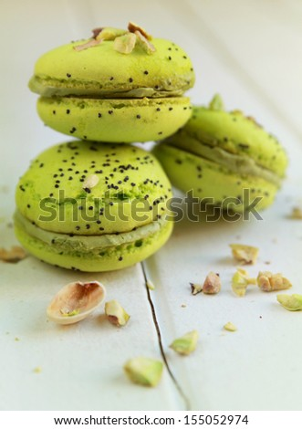 Pistachios macarons on a table with crushed pistachios - stock photo