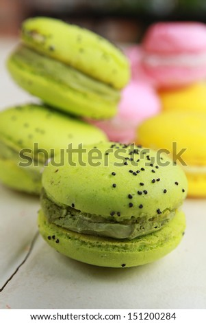 Pistachios macarons on a table with pink and yellow macarons - stock photo