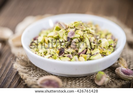 Pistachios (minced)  as detailed close-up shot on vintage background (selective focus)