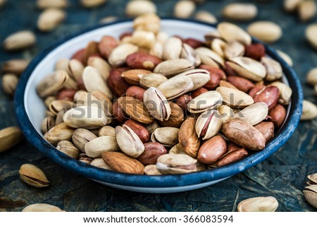Pistachios, nuts, almonds, hazelnuts in white enamel plate on blue wooden background - stock photo