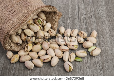 Pistachios nuts  in burlap sack on vintage wooden table - stock photo