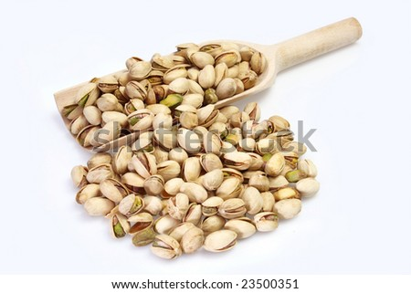 Pistachios on a wood shovel on bright background