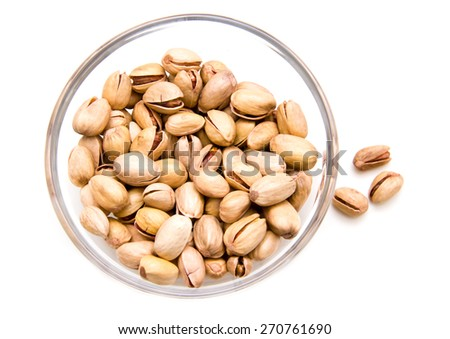 Pistachios on glass bowl on a white background seen from above - stock photo