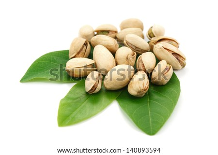 Pistachios on green leaf and white background.