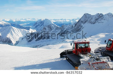 Piste preparation vehicles with view over the alps - stock photo