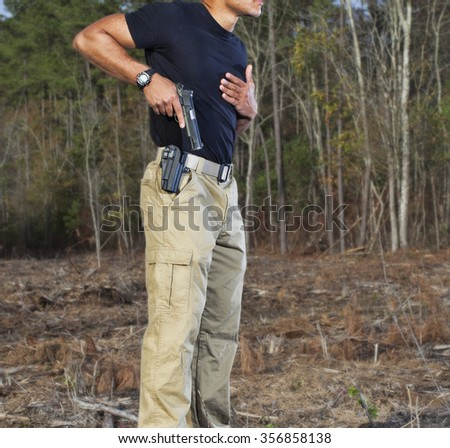 Pistol being drawn from a polymer pistol outdoors - stock photo