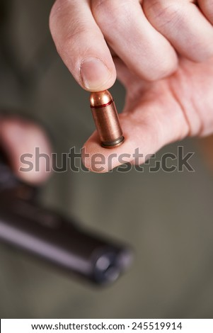 Pistol cartridge in hand shooter on green background - stock photo