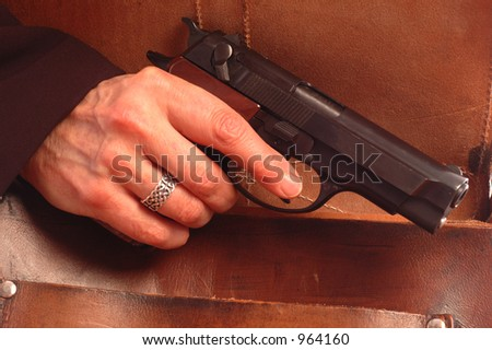 pistol coming from leather bag - stock photo