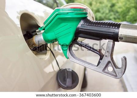 Pistol grip refueling car tank with gasoline - stock photo