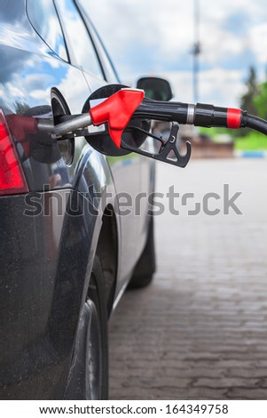 Pistol of gas station is inserted into the tank car for refuel. Close-up view - stock photo