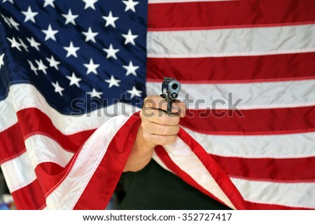 pistol pointed directly at the camera from behind an American flag. Represents Americas 2nd amendment rights to bare arms.