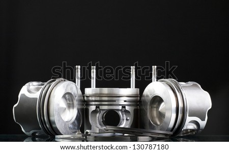 Pistons and accessories isolated on black - stock photo
