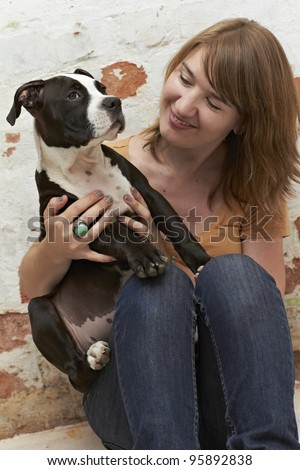 Pit Bull puppy sitting on lap of an attractive young lady - stock photo