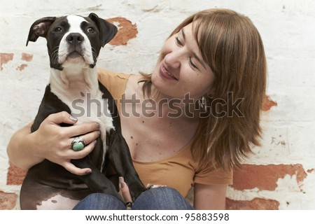 Pit Bull puppy sitting on lap of attractive young pet owner - stock photo