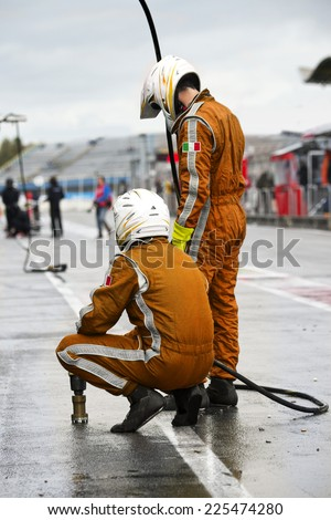 Pit Crew anticipating the arrival of their race car during a tyre change pitstop because of wet race conditions - stock photo