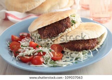 Pita bread filled with breaded steak and cabbage with cherry tomato