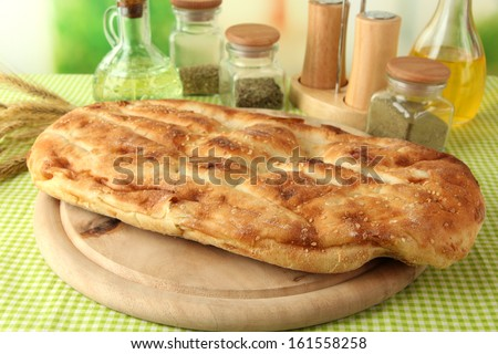 Pita bread on wooden stand with spices on tablecloth on bright background