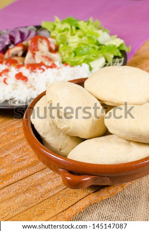 Pita bread, plate with kebab ingredients in the background