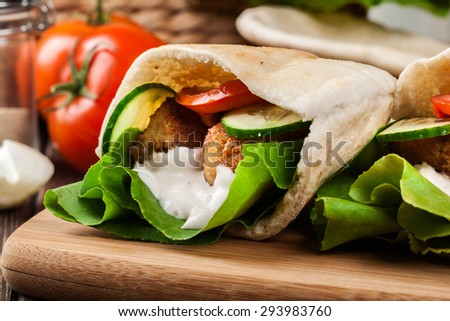 Pita bread with falafel and fresh vegetables on wooden table