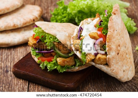 Pita salad with roasted chicken and vegetables, served with a delicious sauce