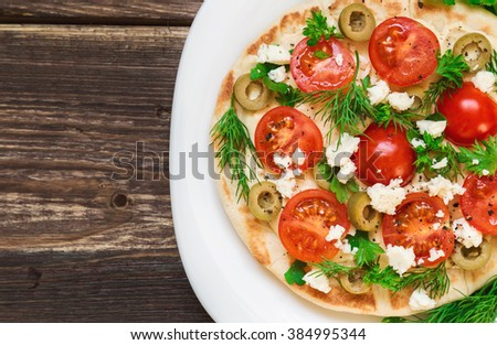 Pita with hummus, cheese, cherry tomatoes, olives and greenery on rustic wooden background.  - stock photo
