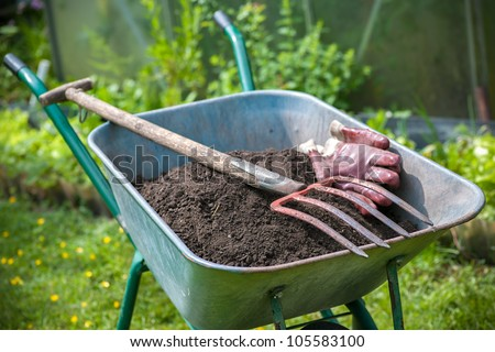 Pitch fork and gardening gloves in wheelbarrow full of humus soil - stock photo
