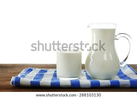 Pitcher and glass of milk on wooden table, on white background - stock photo