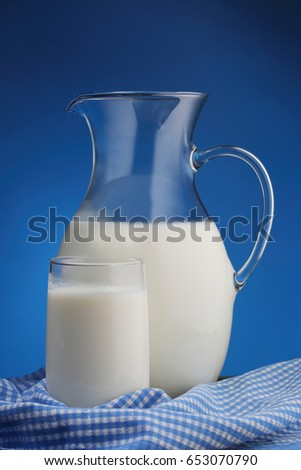 Pitcher and glass with some milk on blue background