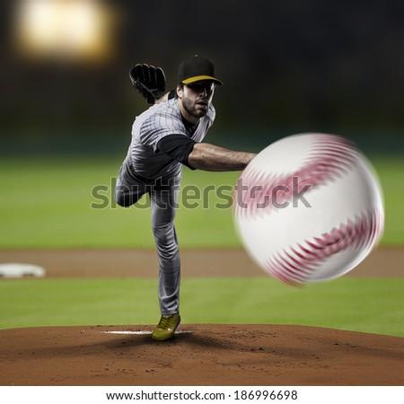 Pitcher Baseball Player on a Yellow Uniform on baseball Stadium. - stock photo