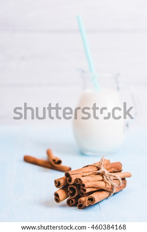 Pitcher glass of milk with cinnamon and cocktail tube on blue wooden background instagram filter - stock photo