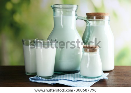 Pitcher, jars and glasses of milk on wooden table, on nature background - stock photo