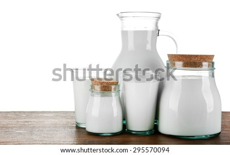 Pitcher, jars and glasses of milk on wooden table, on white background - stock photo