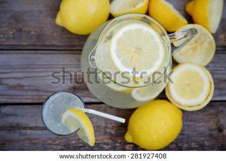 Pitcher of lemonade on a wooden background. Top view, selective focus and space for inscriptions - stock photo