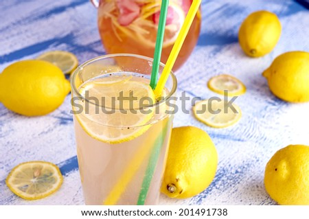 Pitcher of lemonade with lemons, ice and fresh slices on vintage blue wood table - still life - stock photo