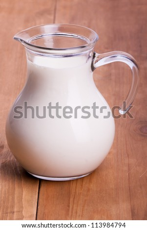 Pitcher of milk on a wooden table - stock photo