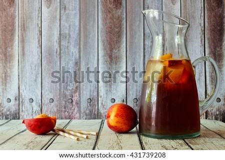 Pitcher of peach iced tea with fruit slices against a rustic wooden background - stock photo