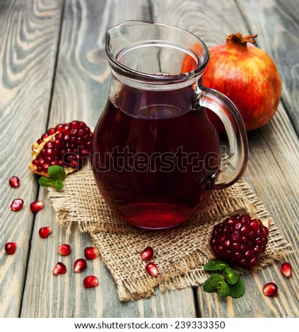 Pitcher  of pomegranate juice with fresh fruits on wooden table - stock photo