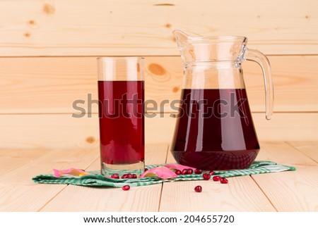 Pitcher of pomegranate juice with pomegranates closeup - stock photo
