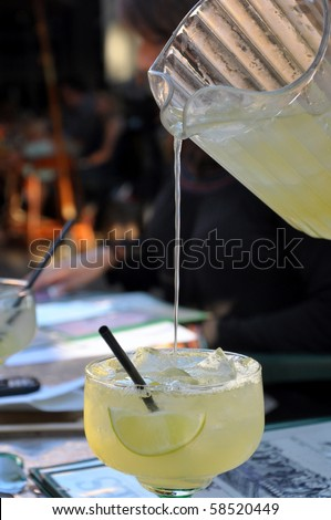 Pitcher pouring liquid into margarita glass.