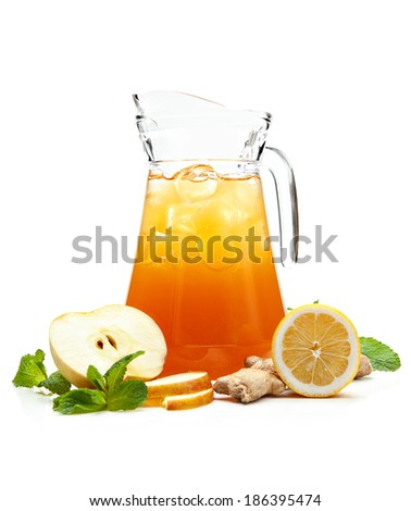 pitcher with a refreshing fruit drink, decorated with fresh ginger and apple on a white background  - stock photo
