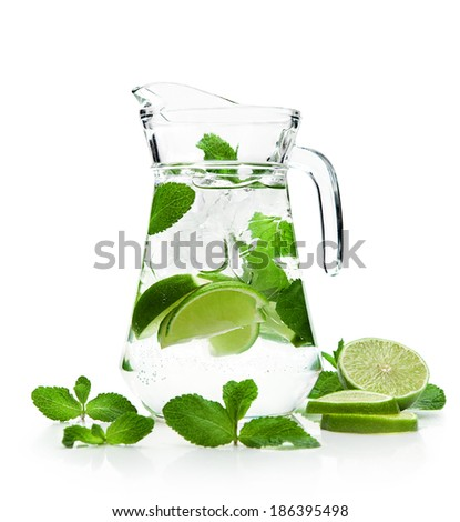 pitcher with a refreshing mojito with fresh mint and lime on a white background  - stock photo